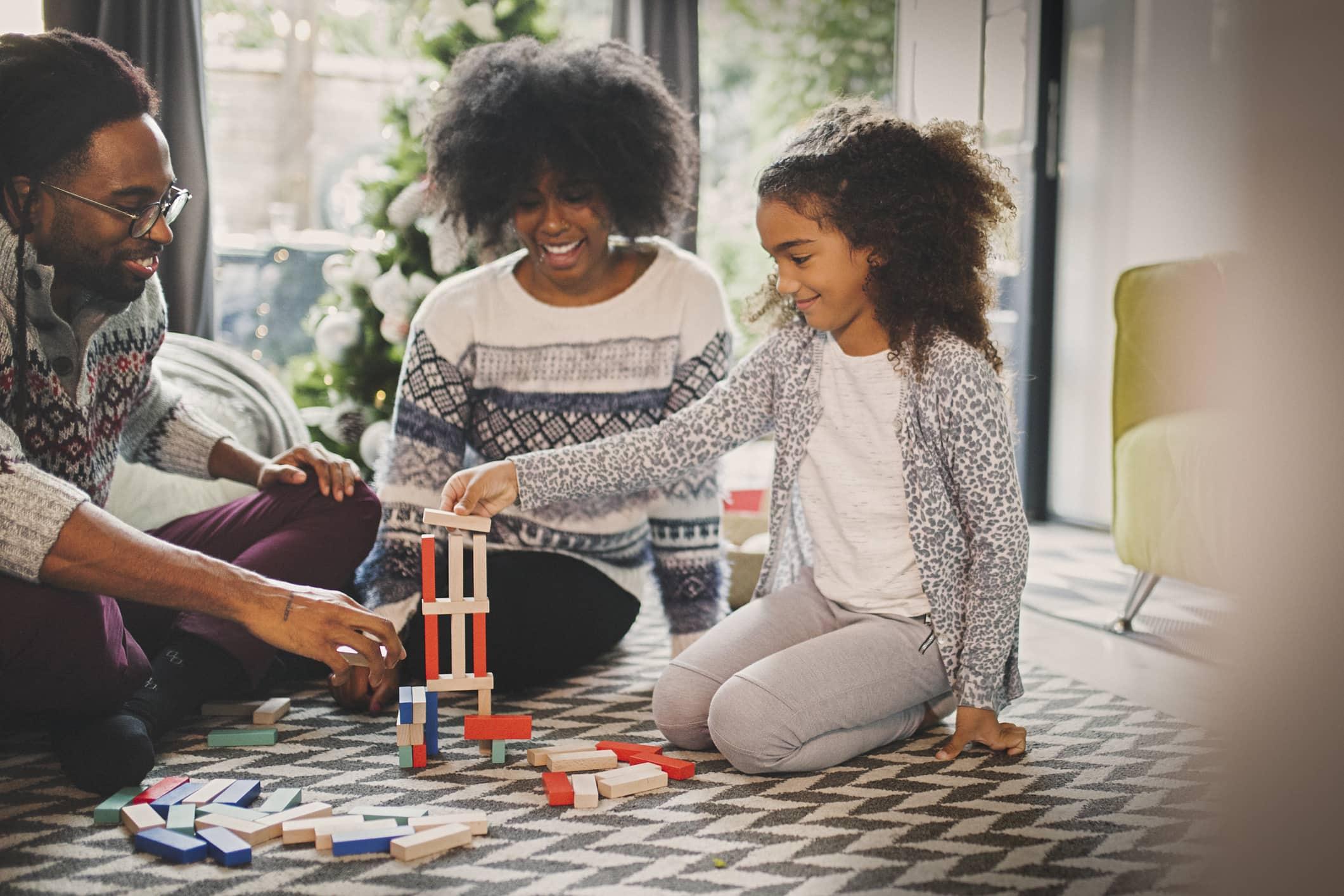 Familie die samen een spel speelt op de vloer van de woonkamer.