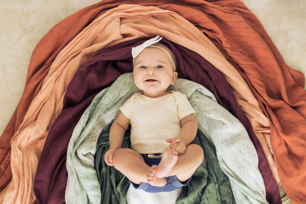 A 5-month-old rainbow baby girl wearing blue shorts, a light yellow shirt and a white bow on top of different color fabric making a warm-colored Autumn rainbow.