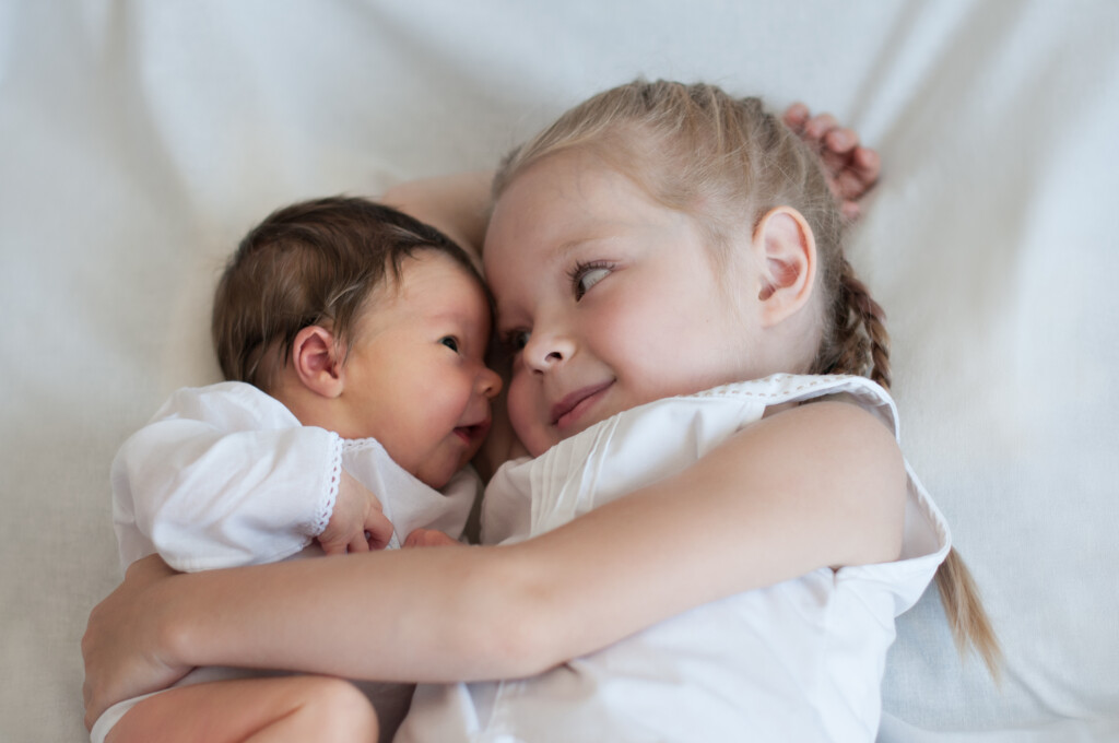 5 years old sister hugs her younger 2 weeks old baby brother.