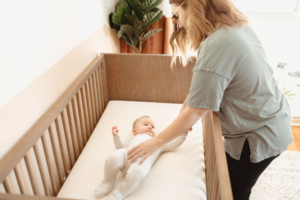 Mother putting her baby down in a safe sleep space on a Naturepedic mattress.