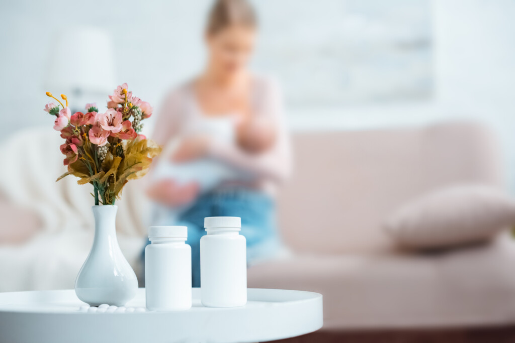 containers with pills, flowers in vase and mother breastfeeding baby behind at home