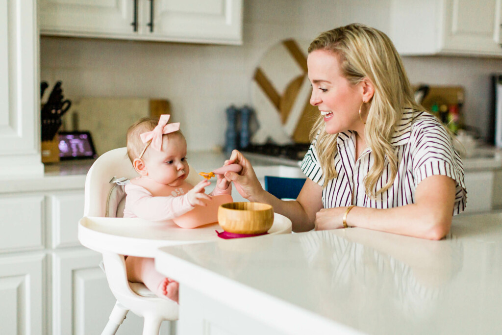 Mother feeding her daughter in her Boon Grub high chair.