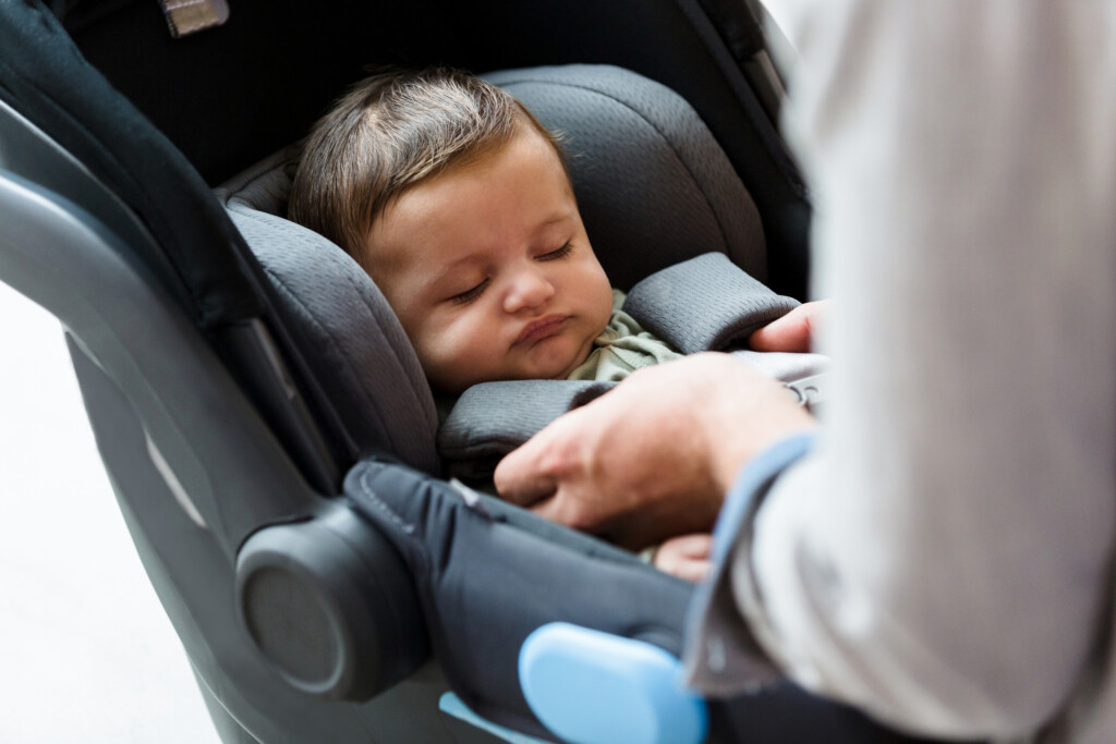 An unrecognizable new dad makes sure his newborn baby boy is strapped securely in an infant car seat.