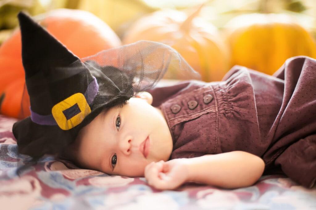 Cute newborn girl wearing witch hat. Orange pumpkins on the background.