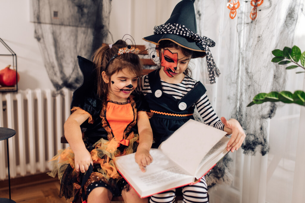 Two cute girls wearing Halloween costumes, playing and reading a book at home.