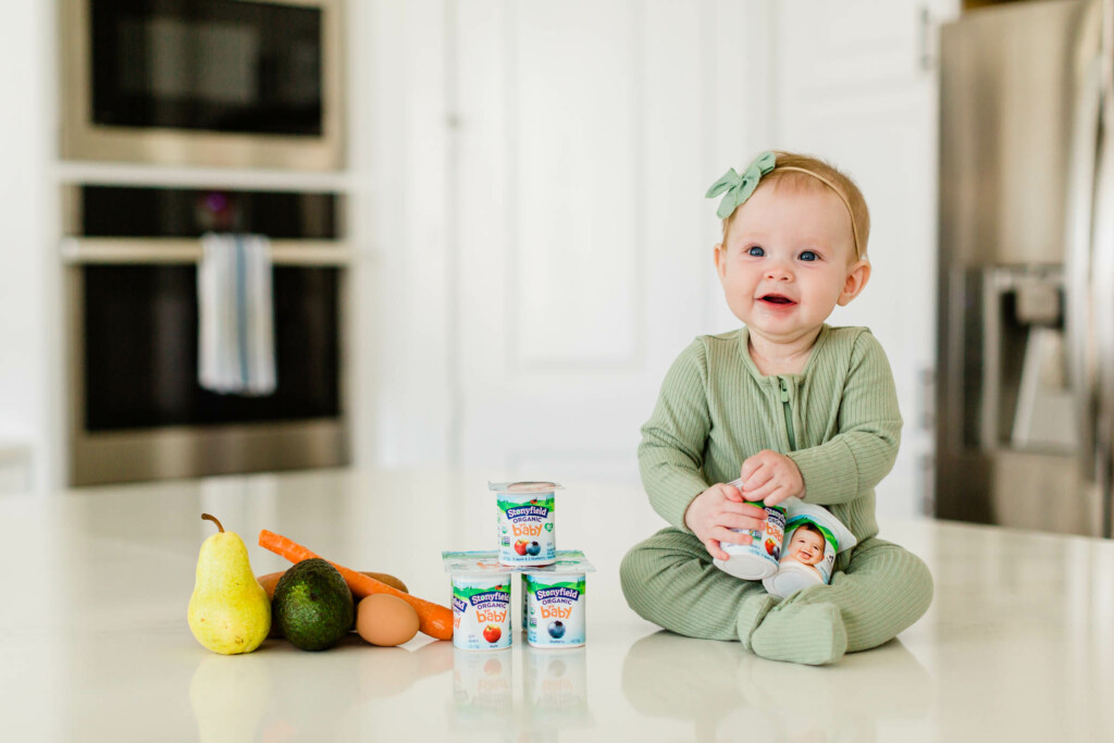 Baby girl sitting on a kitchen counter with solid foods and holding Stonyfield yogurt