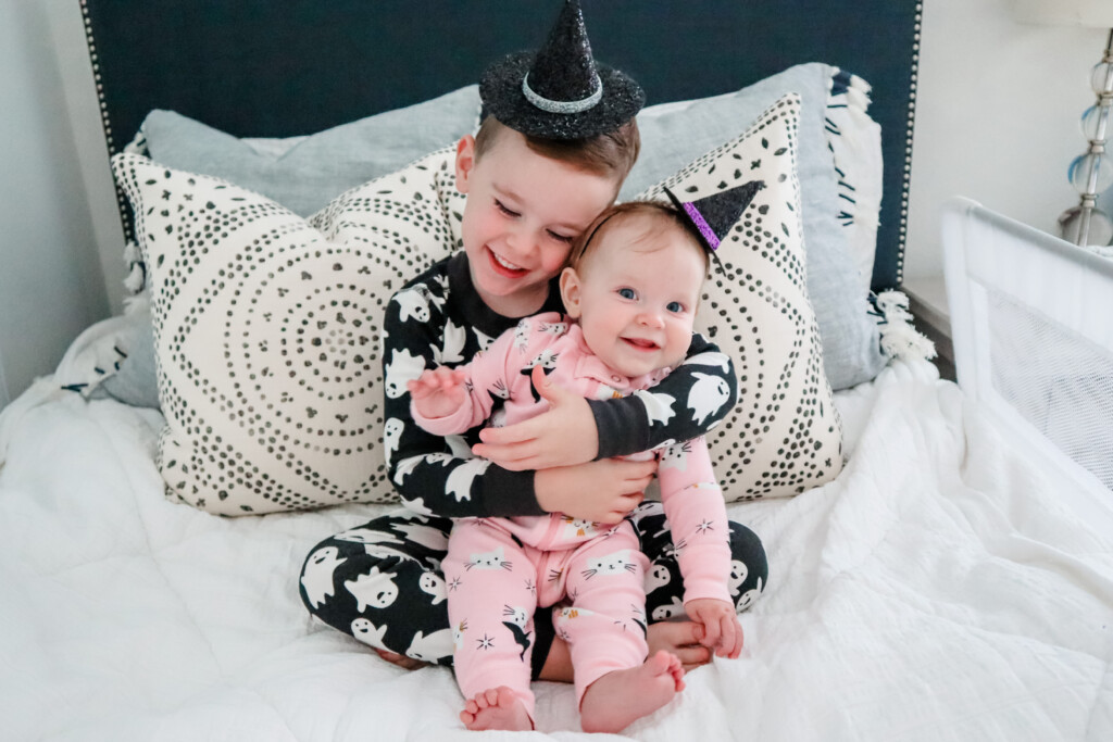 Big brother and baby sister sitting on a bed wearing Halloween pajamas